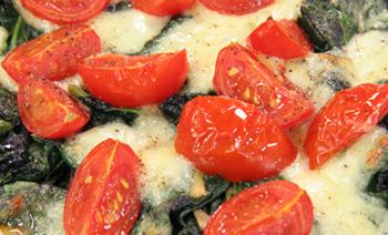 Erdäpfelpizza mit Blattspinat und Paradeiser