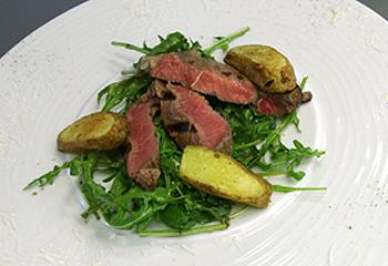 T-Bone-Steak mit Rosmarinkartoffel, dazu Rucolasalat mit Parmesan
