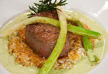 Kleines Filetsteak auf gebratenem Reisfladen mit grünem Paprikaschaum