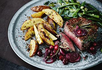 Kräuter-Steaks mit Cranberry-Schalotten, Ofenerdäpfeln und Gemüse Foto: © Janne Peters