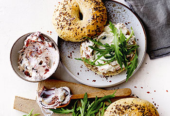 Leinsamen-Bagels mit Tomaten-Oliven-Frischkäse und Rucola Foto: © Janne Peters